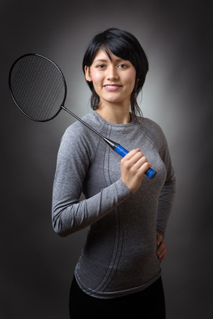 low key lighting: Upper body shot of a slim, pretty, fitness model holding a badminton racquet over her right shoulder, low key lighting shot on a grey background. Stock Photo