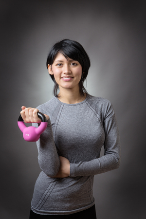 low key lighting: Young sporty woman with pink kettlebell portrait, low key lighting shot on a grey background Stock Photo