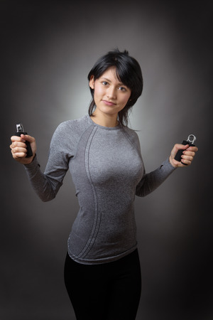 low key lighting: Fitness model doing hand grip exercise for strength.  Low key lighting shot on a grey background.