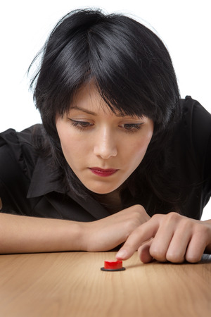poised: Studio shot of a thoughtful model holding her finger poised above a red button on a desk, ready to press it.  isolated on a white background
