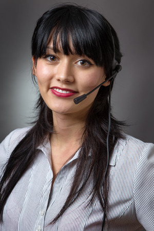 telemarketer: Close up studio shot of an attractive female call center operator, client services assistant or telemarketer wearing a headset looking at the camera with a charming friendly smile