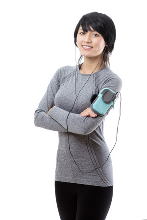 ear phones: Upper body shot of a slim young female model with arms folded, wearing a long sleeved grey top,with a sports arm band, wearing ear phones. Stock Photo