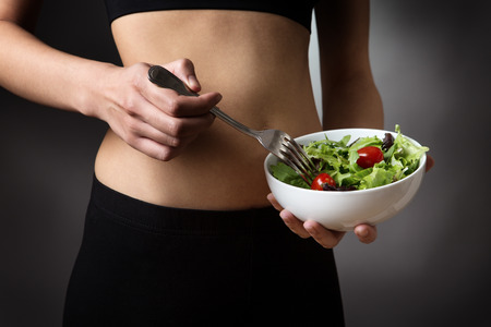 midriff: Close up studio shot of a young sporty woman wearing her gym kit, holding a bowl of healthy salad