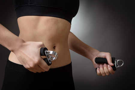 Close up studio shot of a fitness womans abdomen. using hand grip exercise for strength.