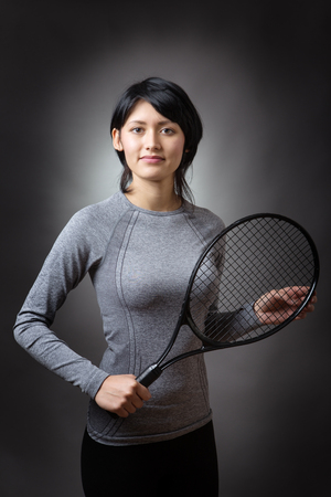 low key lighting: Upper body shot of a slim, pretty, fitness model holding a tennis racquet.  low key lighting on a grey background.