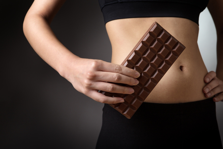 midriff: Close up studio shot of a slim, young, fitness model, holding a large bar of chocolate by her stomach.