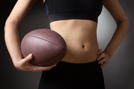 midriff: Close up shot of a slim young models abdomen, whilst holding a rugby ball. Low key lighting shot on a grey background