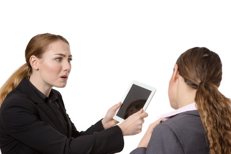 aghast: Close up studio shot of two pretty business women.  One is looking very concerned about the tablet computer in her hand.  The other woman is seen from behind.  isolated on white