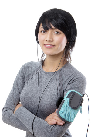 ear phones: Close up portrait shot of a slim young female model with arms folded, wearing a long sleeved grey top,with a sports arm band, wearing ear phones.