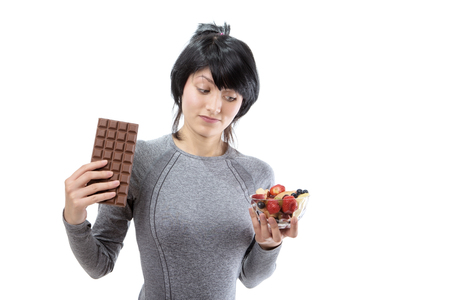 decide deciding: fitness model wearing a grey long sleeved top, trying to decide between a big bar of chocolate and a fruit salad.