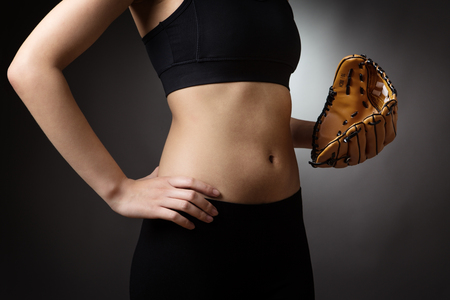 midriff: Close up shot of a slim young models abdomen, whilst wearing a baseball glove close to her abdomen on her left hand and her right hand on her hip.
