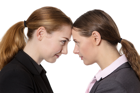 knocking: Close up office shot of two businesswomen knocking their heads together.