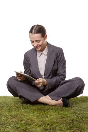 pleased: Studio shot of a beautiful business woman, sitting crossed legged on the grass, using a tablet computer.  The woman is looking very happy and pleased.