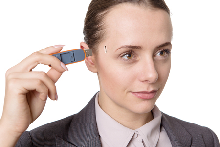 memory stick: Head and shoulders studio shot of a pretty business model holding a usb memory stick to the side of her head