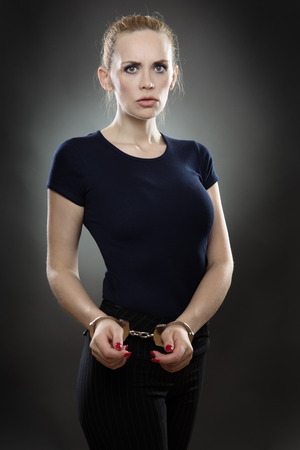 handcuffed: business woman with her wrists handcuffed together looking worried.