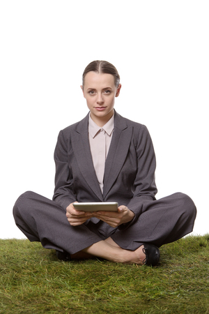 cross legs: serious business woman sitting with cross legs on the grass, whilst holding a tablet computer,  isoalted on white background
