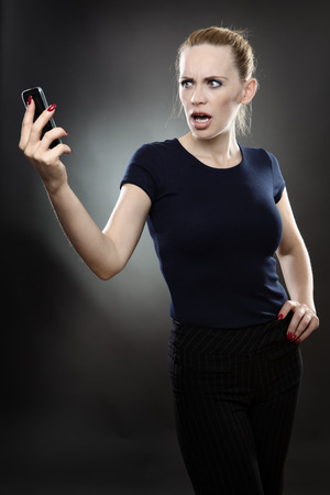 disbelief: Pretty business woman is staring at her mobile phone in disbelief with a shocked expression on her face. Shot on a grey background