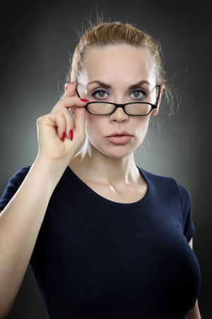 reaching up: Studio shot of an attractive, serious looking business woman wearing glasses, with her hair tied back away from her face.  she is reaching up and holding the glasses.