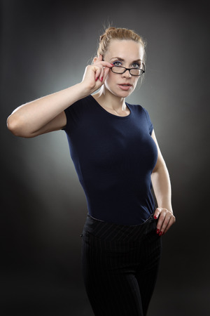 buisness woman: studio shot of businesswoman wearing glasses.  shot on a grey background