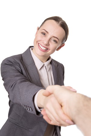 shaking out: Close up shot of a happy female business model reaching out and shaking a mans hands. Stock Photo