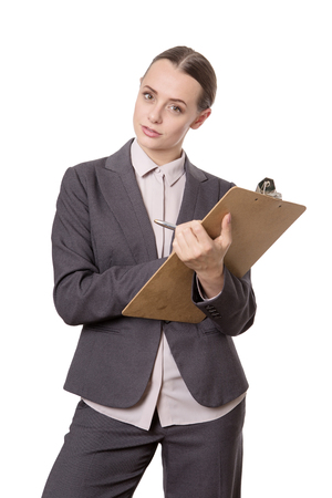 poised: serious looking female business model, wearing a suit, holding a clipboard and pen, poised ready to write.