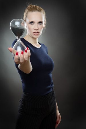 trickling: Studio shot of a pretty business model holding a large sandtimer out infront of her.  Black sand is trickling through the hour glass. Stock Photo