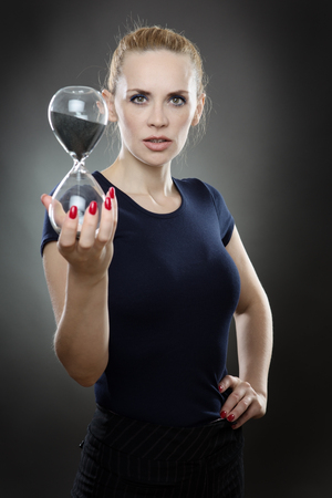 run out: Studio shot of a pretty business model holding a large sandtimer out infront of her.  Black sand is trickling through the hour glass.  Watching the sand of time run out.