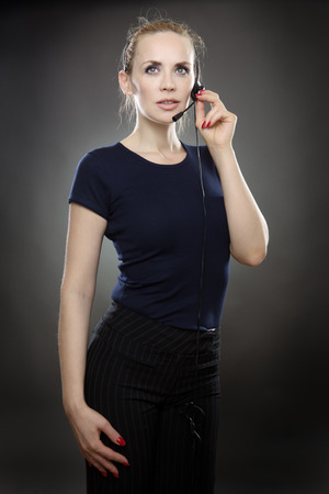 handsfree: business woman talking on a handsfree headset.  shot on a grey background.