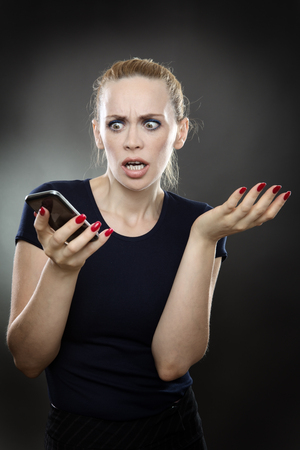 disbelief: business woman is staring at her mobile phone in disbelief with a shocked expression on her face. Stock Photo