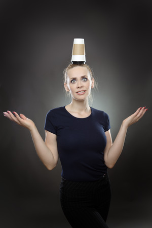 misconception: Studio shot of a   business woman with a takeaway cup balanced on her head.  Shot on a grey background. Stock Photo