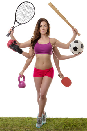 arm holding: fitness woman with six arm holding different sports items standing on grass shot in the studio