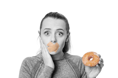 split lip: woman with first aid plaster over mouth unable to eat a donut
