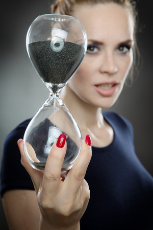 run out: Studio shot of a pretty business model holding a large sandtimer watching the sand of time run out.  Shot on a grey background