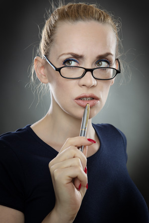 to ponder: Studio shot of a thoughtful business woman wearing glasses.  shot on a grey background