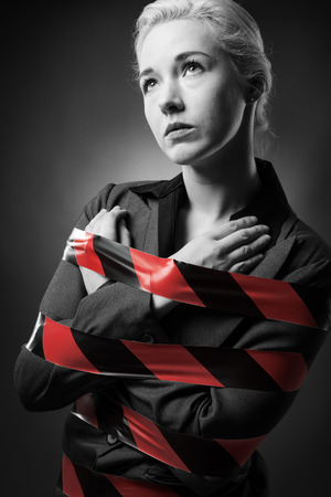 Business woman wrapped up in red tape