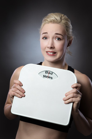 bad news: woman holding scales looking worried with the words bad news written on the scales Stock Photo