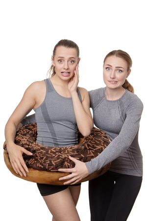 concept idea of two woman one with a large donut around her waist worried about weight gain photo