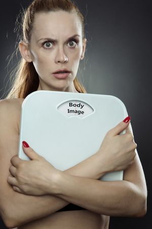 low key lighting: woman shot in the studio, low key lighting holding weight scales with the words body image printed on the scales disk