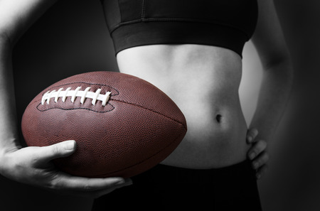 low key lighting: Close up shot of a slim young models abdomen, whilst holding a american football close to her abdomen. Low key lighting shot on a grey background