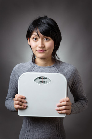 body image: woman holding bathroom scales with the word body image written on the weight dial
