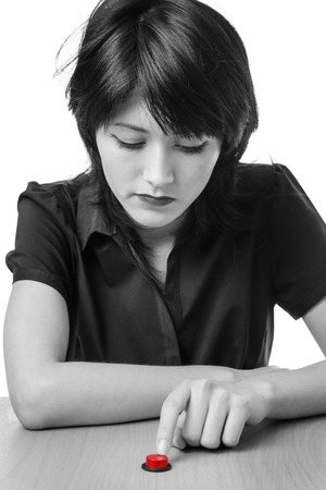 poised: Studio shot of a thoughtful model holding her finger poised above a red button on a desk, ready to press it.