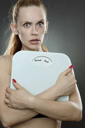 low key lighting: woman shot in the studio, low key lighting holding weight scales with the words Good bad printed on the scales disk Stock Photo