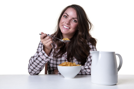 pj's: Studio shot of a pretty model wearing her pjs, sitting at the breakfast table, eating her breakfast in the morning.  isolated on a white background.