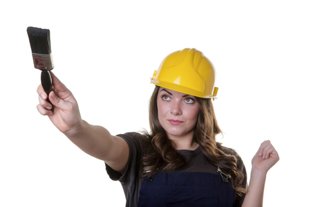 yellow hard hat: upper body studio shot of a pretty model wearing a yellow hard hat on her head and holding a paint brush in her right hand. Stock Photo