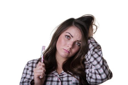 pj's: Close up studio shot of a sleepy looking model wearing her pyjamas and a toothbrush.  Isoalted on white background.