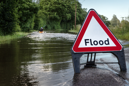 county road in essex of flooded road with a person paddling  down the road in a kayak Standard-Bild