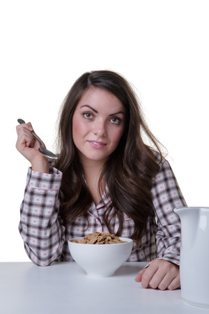 pj's: studio shot of a pretty model wearing her pyjamas, sitting at a table, eating her bowl of breakfast cereal.