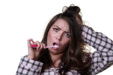 wellness sleepy: Close up studio shot of a sleepy looking model wearing her pyjamas and a toothbrush.  Isoalted on white background.