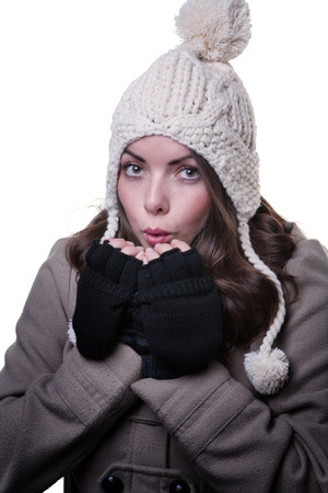 bobble: Close up shot of a model wearing a winter coat, knitted woollen, fingerless gloves and a cream bobble hat.