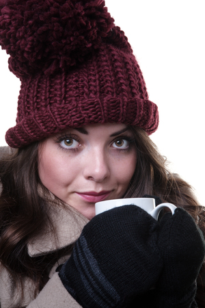 woollen: Close up studio shot of a young, pretty model, wearing an woollen winter hat, coat and gloves,whilst holding a mug.